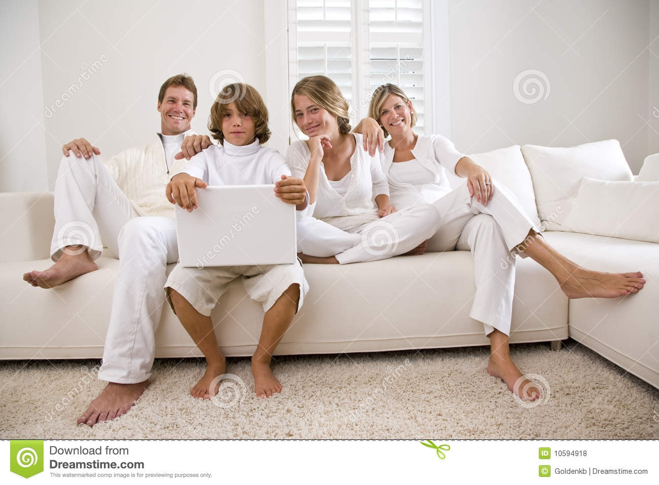 Family Relaxing At Home On White Living Room Sofa Royalty Free Pertaining To Family Sofa (#4 of 12)