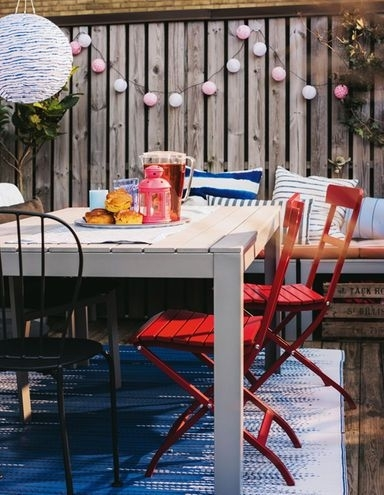 An Outdoor Dining Table With A Lantern, A Plate Of Pastries, And Inside Red Outdoor Table Lanterns (View 8 of 15)